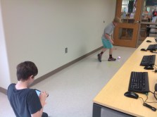 Students take turns programming robots to move from one square to another.