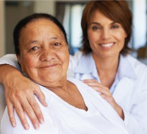 Care giver with her arm around a senior resident