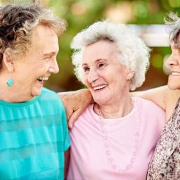 Three senior women friends smiling and laughing outdoors