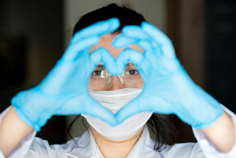 Female healthcare worker with blue gloves, mask and goggles.