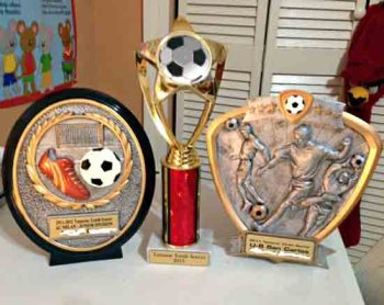 Parent displays their custom trophies on left and right that has their child's name and in the middle, the generic on that is given out by the City of Tamarac