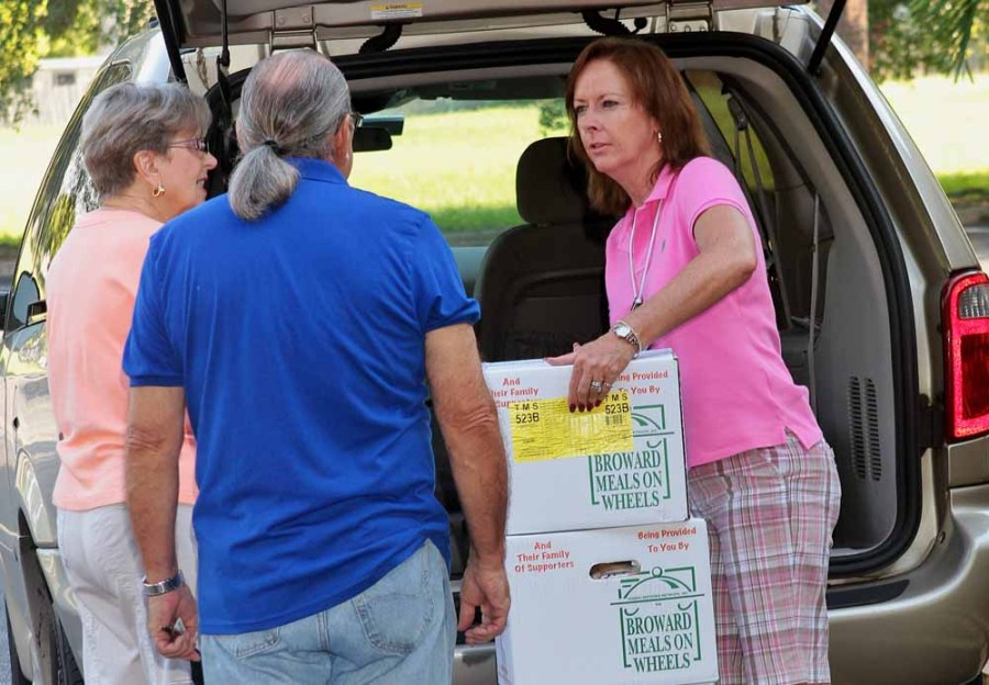 Tamarac Volunteer Lisa Mattson passing out Meals on Wheels boxes to those on her route.