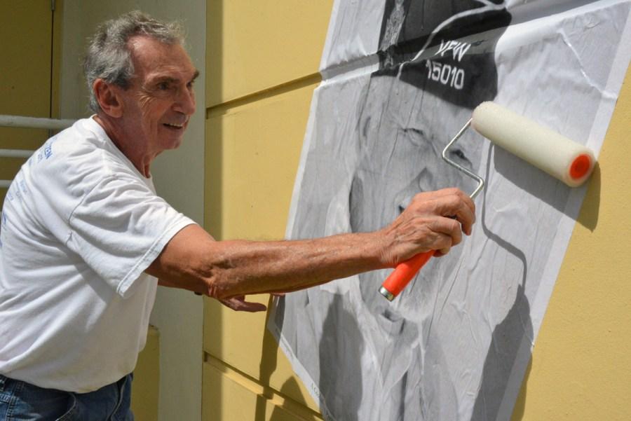 Resident Herbert Haber hanging up one of the many photos displayed around the Tamarac Community Center