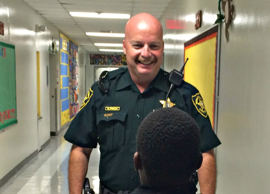 SRO Officer Barry French speaks to a student. French is busy splitting his time between two schools: Tamarac Elementary and Challenger Elementary.
