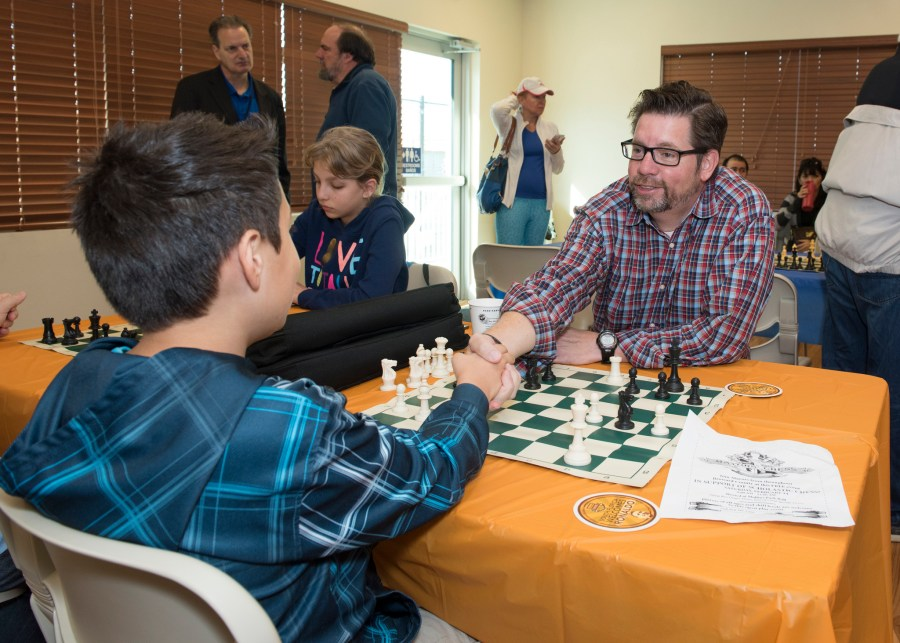 Sunrise Mayor Mike Ryan who helped start the Mayor's Chess Challenge begins a friendly game with a competitor in Coral Springs