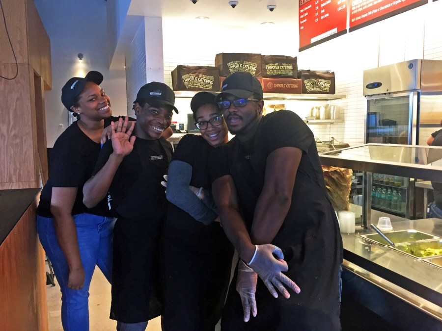Chipotle employees pose for a photo.