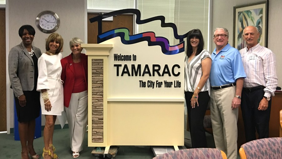 New signage was unveiled at the commission workshop on Monday. L to R: Community Development Director Maxine Calloway, Commissioners Debra Placko, Pamela Bushnell, Michelle Gomez, Mayor Harry Dressler and Baron Sign Manufacturing President Jerry Foland