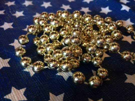 Golden Mardi Gras Beads; 1,127 ppm Lead (Pb)