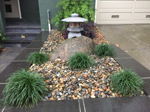 Close up of Asian accent, stone lantern and green accents in a bed of river pebbles