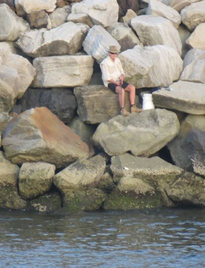 This fisherman seems to have deliberately camouflaged himself to blend in with the rock wall - can fish see that far?
