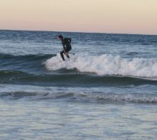 A young surfer takes advantage of the last of the light to tackle a baby wave