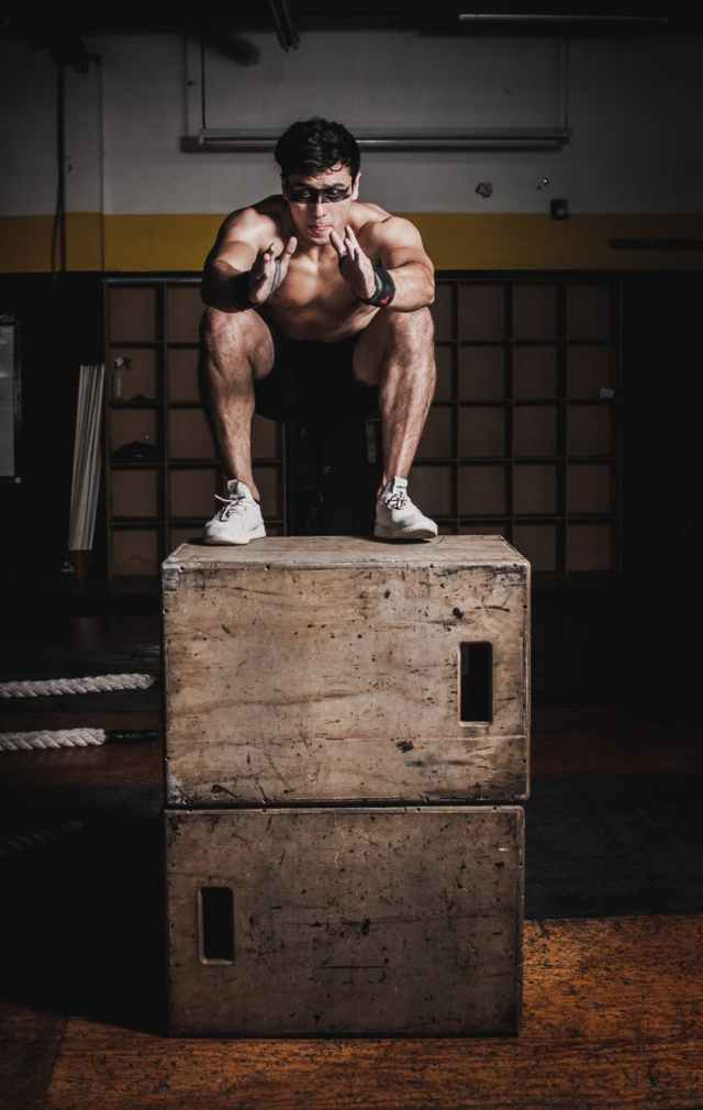 man doing squats on brown wooden box