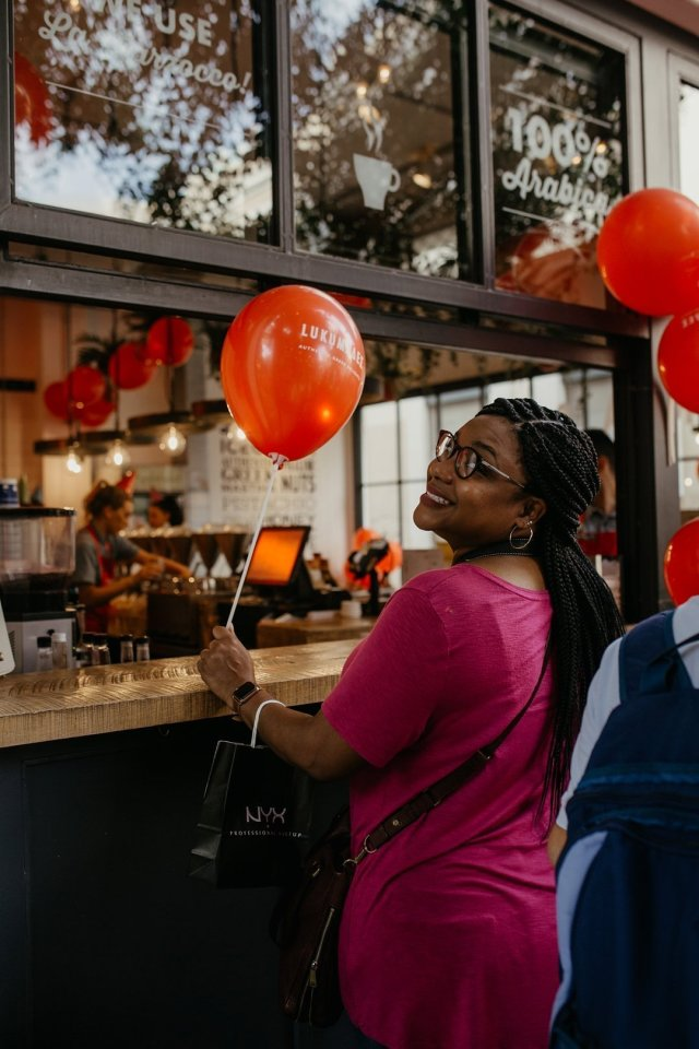 Girl with red balloons smiles at the camera at Lukumades in Athens Greece.