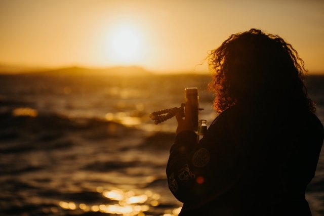 Woman capturing Sunset at Galleraki's Cocktail bar in Little Venice of Mykonos Town by Tami Keehn