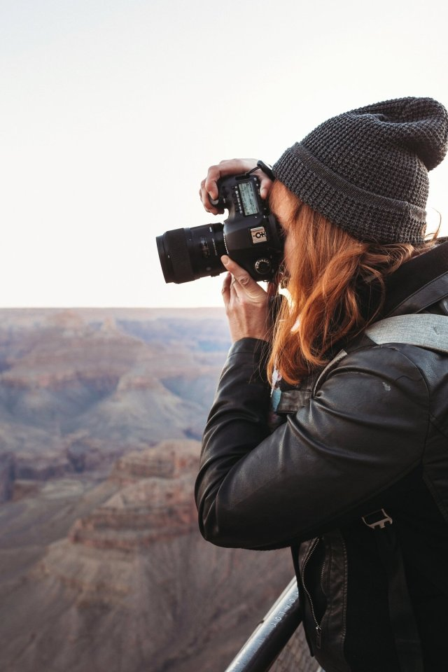 A redhead photographing sunset at Hopi Point on the South Rim of the Grand Canyon by photographer Jennifer Kielich