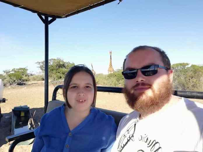 couple on game drive with giraffe