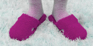 woman's feet with fuzzy pink slippers