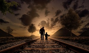 Man walking with child on train tracks