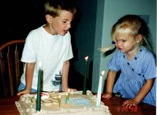 Two children blowing out candles on a birthday cake.