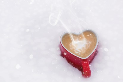 Heart cup with coffee in snow