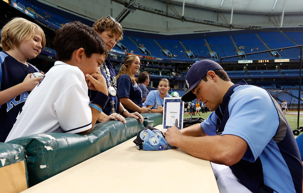I'll concede the point, Matt Moore is signing an autograph, not writing for X-Rays Spex. However, I challenge you to find a photograph of baseball players writing for a blog.