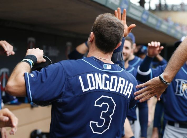 Evan Longoria is greeted in the dugout after scoring on a hit by David DeJesus in the sixth inning on Sunday. Both Longoria and James Loney drove in the runs. (Photo credit: AP Photo/Jim Mone)