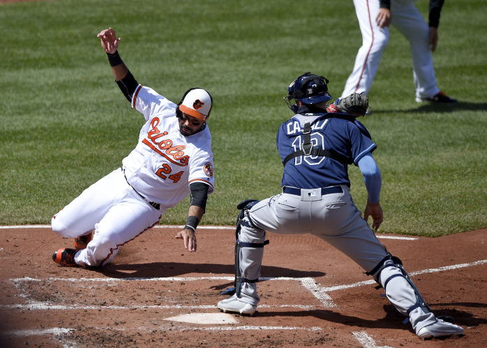 Baltimore Orioles' Pedro Alvarez, left, slides home to score against Tampa Bay Rays catcher Curt Casali on a double by Jonathan Schoop during the second inning of an baseball game, Sunday, April 10, 2016, in Baltimore. (AP Photo/Nick Wass)