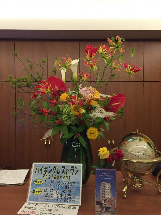 松、千両、カラー(ウェディングマーチ)、グロリオサ、アンスリウム、ラナンキュラス、アジサイ、晒ヤマシダ、紅白の水引と正月飾り