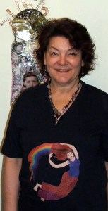 Photo of Tammy Vitale is wearing Tangerine Meg Rainbow Lady tshirt design, along with one of her own necklaces, in front of her own beautiful sculpture