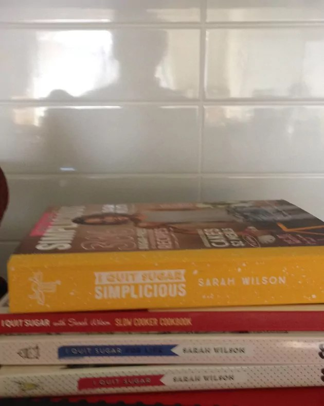 I quit sugar cookbooks in the foreground, with a reflection of me in the white tiles above