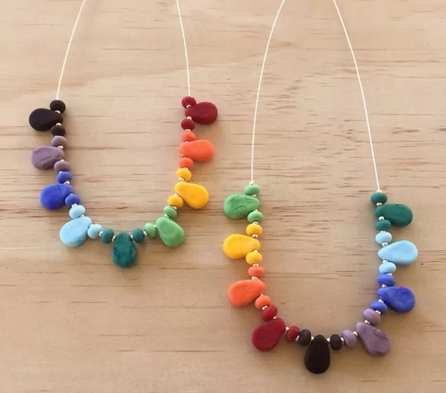 2 rainbow drop glass necklaces on wooden background