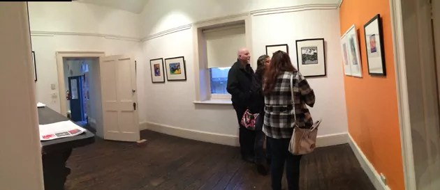 gallery patrons discussing art at a gallery launch