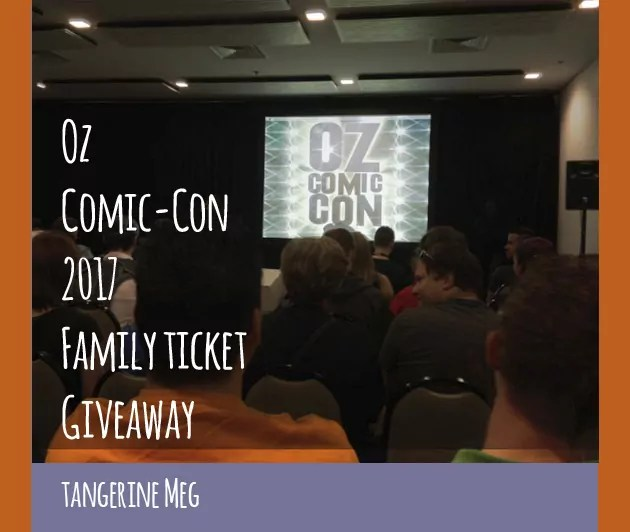 """photo of convention room, showing audience heads chatting while they wait for a talk; on stage is a screen with the 2014 Oz Comic-Con logo of 2014; overlaid is blog post header in hand-writing looking font stating: """" Oz Comic-Con 2017 Family Ticket Giveaway - Tangerine Meg"""". There's a purple border at the bottom and orange borders at the sides."""