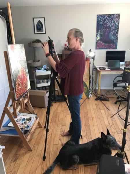 Tricia taking photos of her art in the middle of her studio