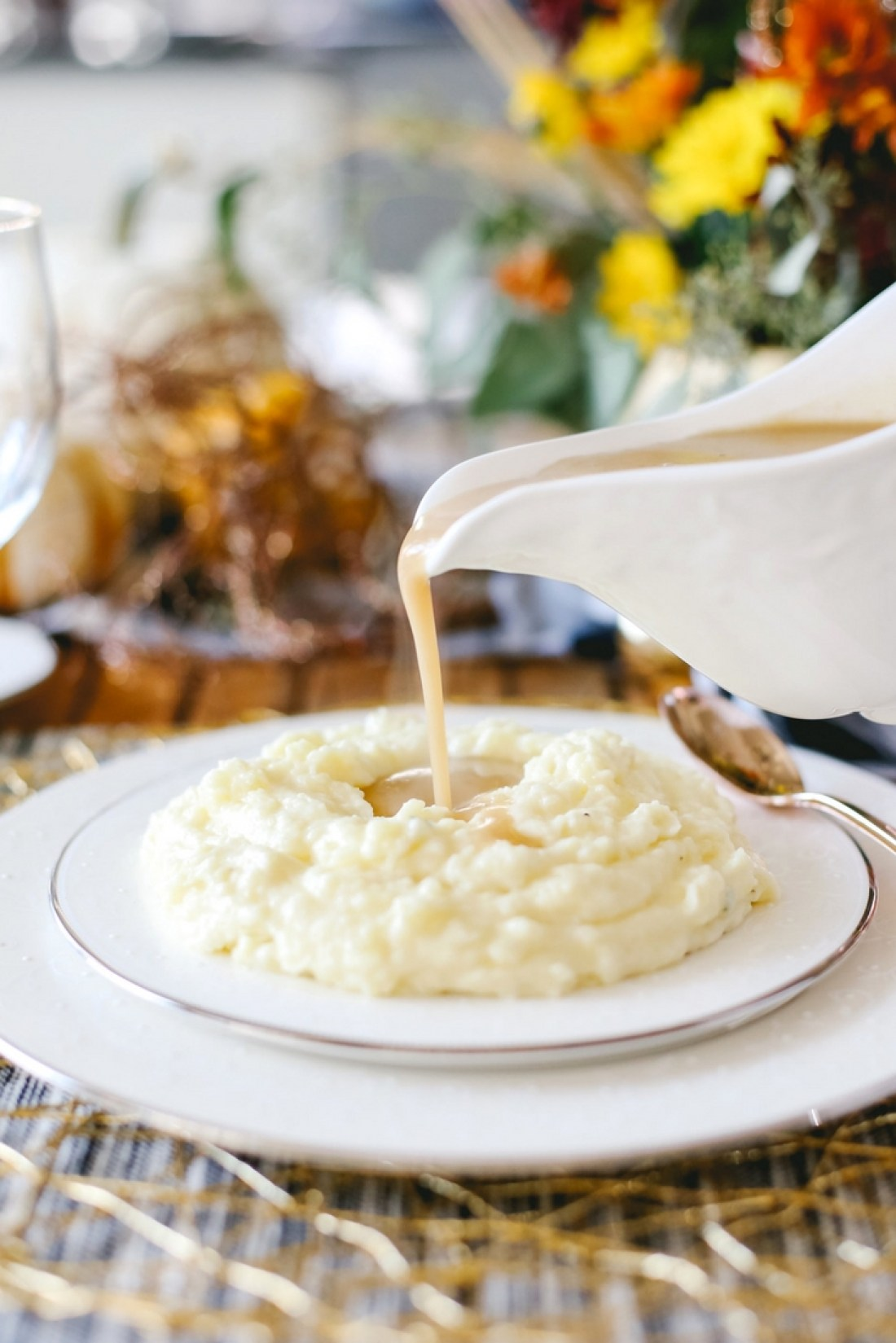 The trick to perfect creamy mashed potatoes is boiling the whole potatoes, then quickly peeling and mashing them together with milk, cream, butter and salt.