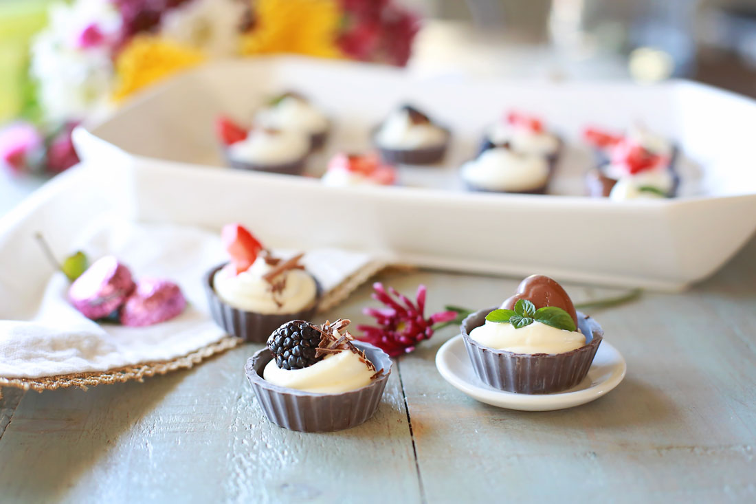Fast, easy, & delicious miniature no-bake chocolate cheesecakes. Light & fluffy cheesecake filling piped into a chocolate shell, topped with goodies.