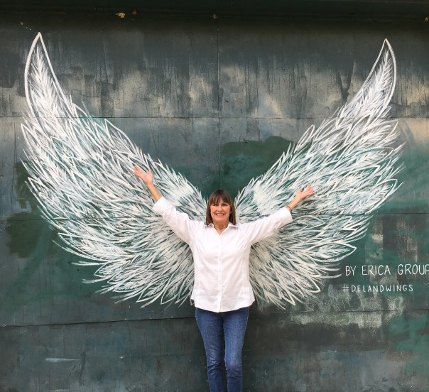 Pose-in-front-of-the-DeLand-Wings-created-by-area-artist-Erica-Group