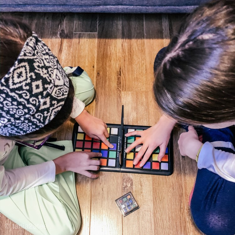 two girls playing Rubik's Race game moving colourful tiles