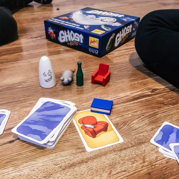 close-up of game pieces including cards and minature red chair, green bottle, grey mouse, white ghost and blue book.