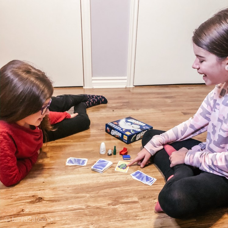 girls playing board game looking at cards