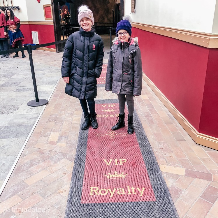 Two-girls-at-Medieval-Times-in-front-of-rug-that-says-VIP-Royalty