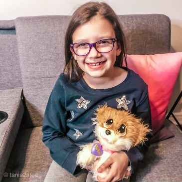 little girls with glasses holding stuffed puppy