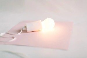 A soft pink fabric with a lightbulb switched on. Soft pink hues all around