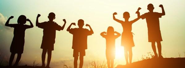 """Des enfants montrant leurs bras """"musclés"""" à contre-jour."""