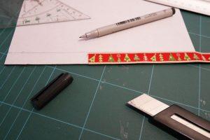 Die Breite des Bands abmessen und auf der Magnetfolie (parallel zur Schmalseite, = ca. 21 cm lang) einzeichnen