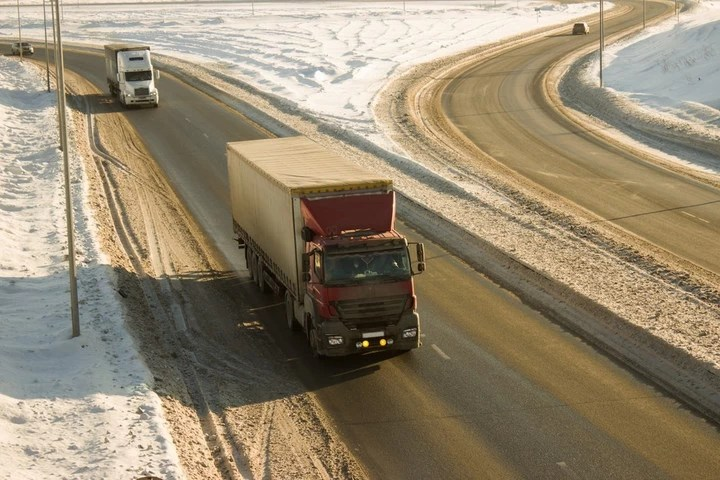 Trucks on snowy winter highway road