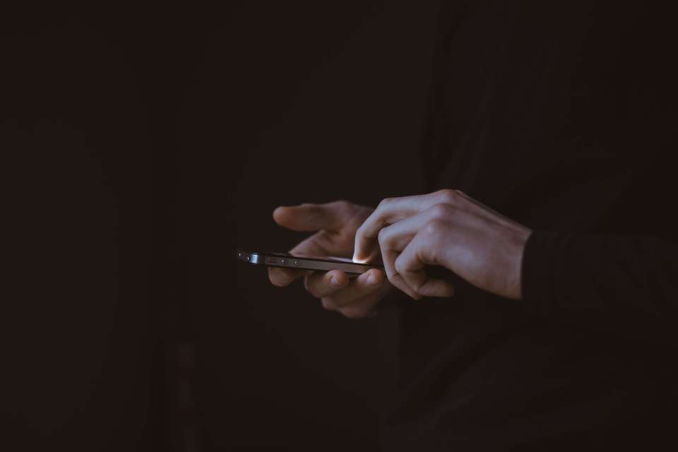 a silhouette of hands and a smartphone