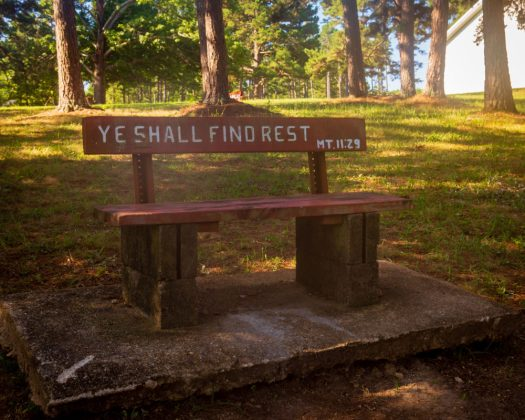 "A wooden bench in a tree lined park at Missionary Acres that reads ""Ye Shall Find Rest."""
