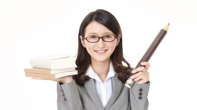本と鉛筆を持った教師