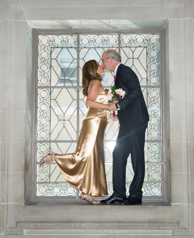Bride and groom kissing in window at City Hall